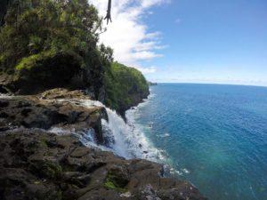 Waterfall into ocean waves Hawaii